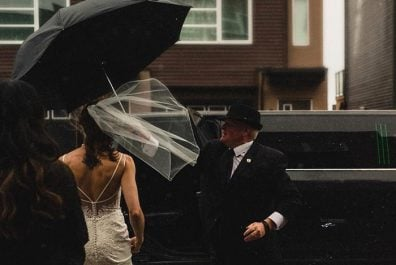 Limo driver holding umbrella for bride as she gets into limo with her gown blowing in the wind