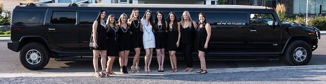 Group of ladies pose in front of black Hummer Limo