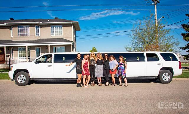 Group of ladies posing for photo in front of white Suburban limousine