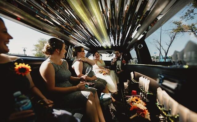 Wedding party celebrating inside of stretch limousine