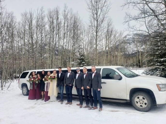 Wedding party photo with white Suburban Limousine