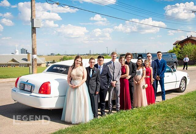 Group of high school graduates standing in front of a white Lincoln Stretch limousine