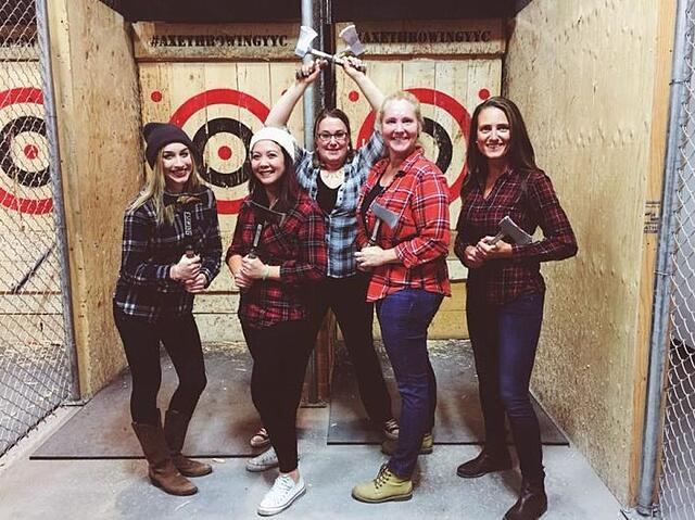Ladies celebrating bachelorette party by axe throwing