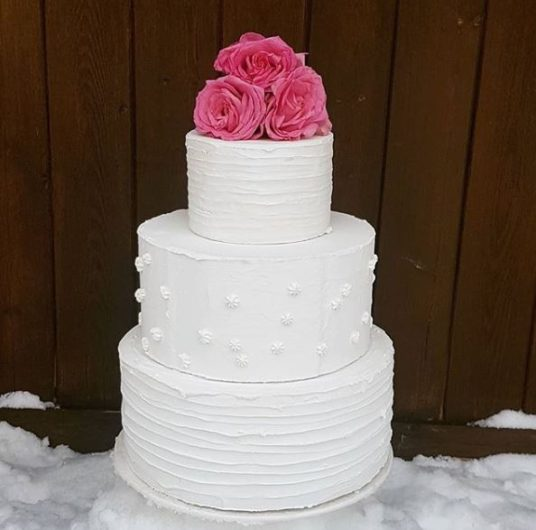 White 3 tier wedding cake with 3 pink edible flowers on top