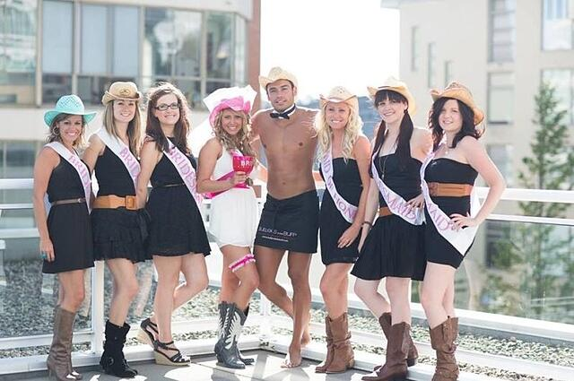 Ladies celebrating bachelorette party with a half naked male
