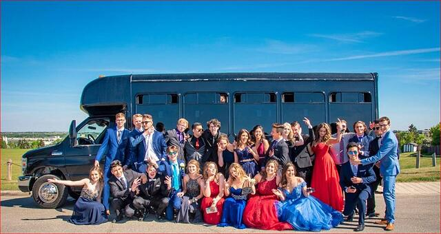 High school grads dressed up for prom, posing in front of a black party bus