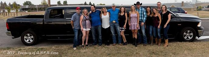 Group of adults with cowboy hats celebrating in front of black Dodge Ram limousine