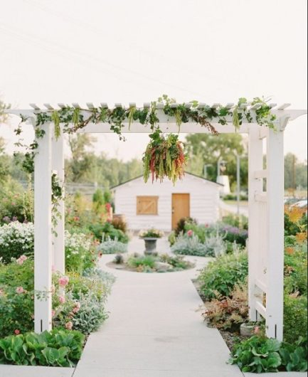Deane House outdoor wedding ceremony area with white arches to walk under into a garden