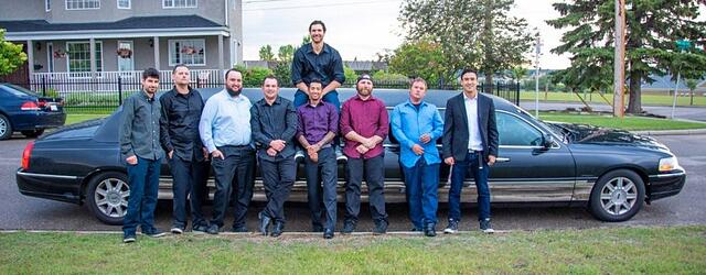 Group of guys posing for photo with black Lincoln Stretch limousine