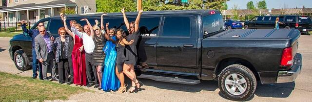 Group celebrating in front of black Dodge Ram Limo
