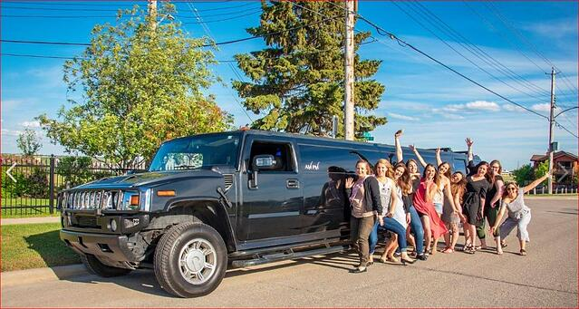 Group celebrating with black Hummer Limousine