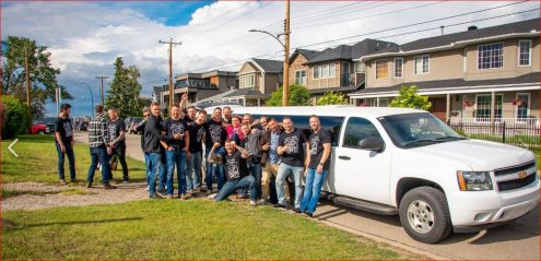 Stag party celebration photo in front of a White Suburban Limousine