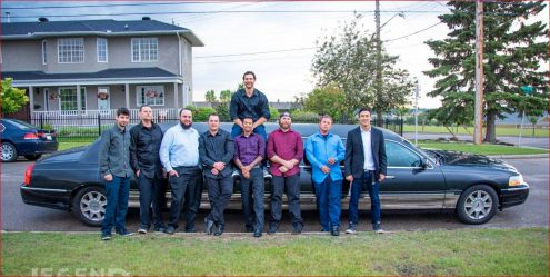 8 guys standing in front of and one man sitting on top of a Black Lincoln Stretch Limousine