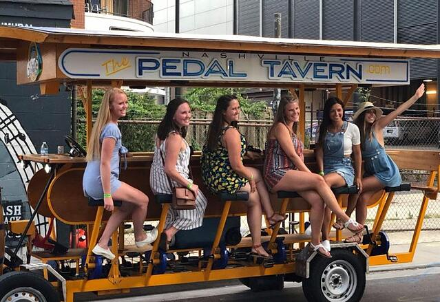 6 ladies on the Pedal Tavern smiling for photo