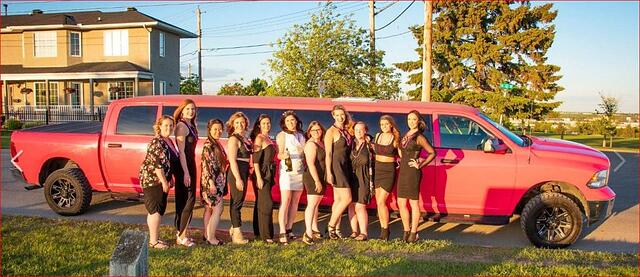 Ladies in black dresses standing in front of the pink dodge ram limousine