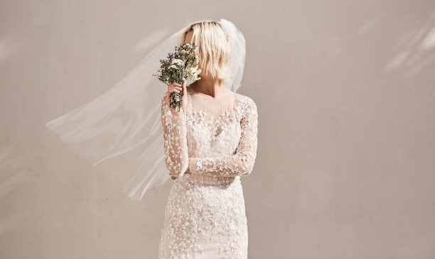 Bride in white wedding gown, holding bouquet in front of her face
