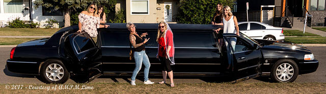Ladies standing up in all 4 doors of black Lincoln Stretch Limo