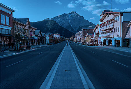 An empty Main Street in Banff Alberta with Rocky Mountians in the distance