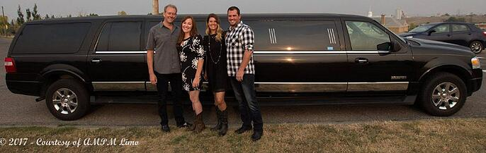 4 people posing for photo in front of black Expedition Limousine