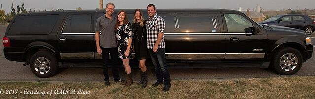 Two couples stand in front of black Expedition Limousine for photo
