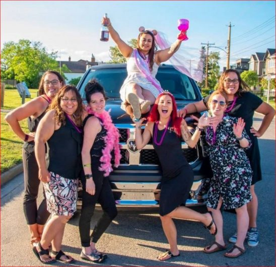 Stagette celebration photo in front of Dodge Ram Limo with bride to be sitting on the hood