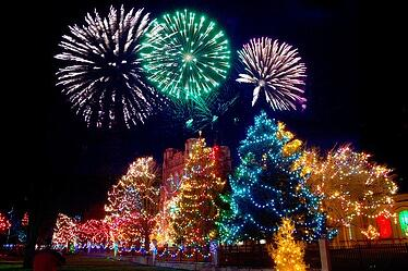 Fireworks going off above huge, fully lit Christmas Trees