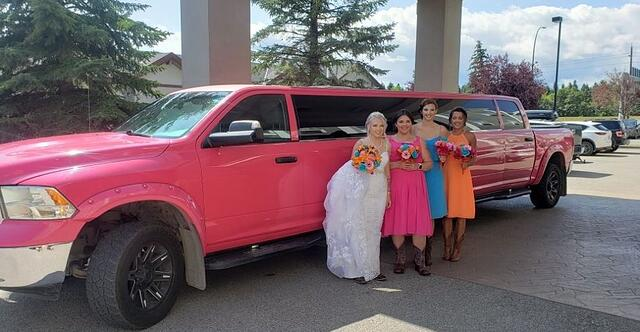 Bride and 3 bridesmaids standing with pink Dodge Ram Limousine