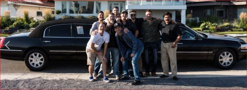 Group of guys at a stag party pose for photo with a black Lincoln Stretch Limousine