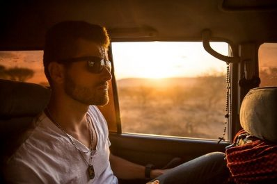 Man sitting in the back of a car with sunglasses on
