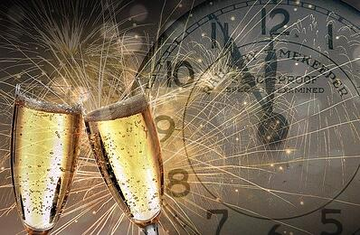 2 glasses of champagne in front of clock that is 5 minutes to midnight onNew Year's Eve