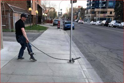 Man standing on sidewalk with a chain from his ankle to a metal pole with a metal male body part attached for stag party
