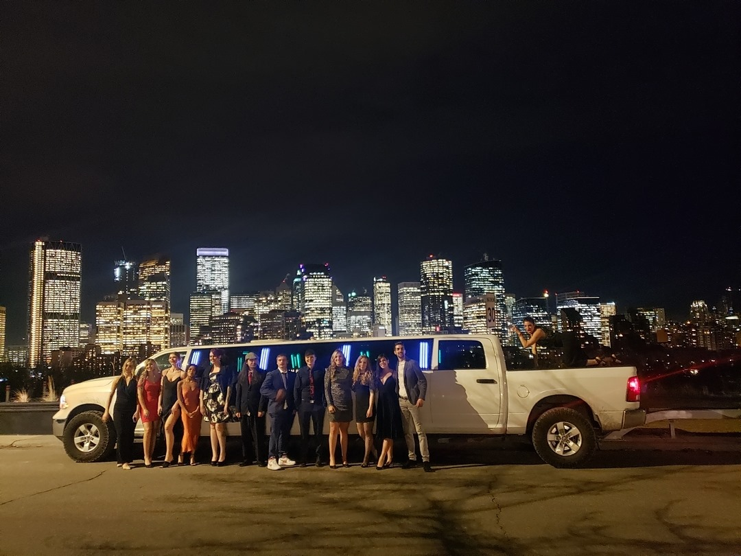 Group photo in front of white Dodge Ram Limousine and city of Calgary skyline at night
