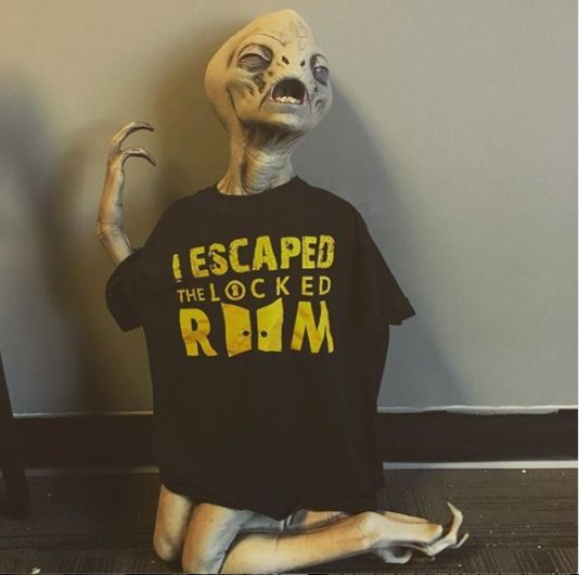 "photo of an alien prop wearing an ""I escaped the Locked Room"" t-shirt"
