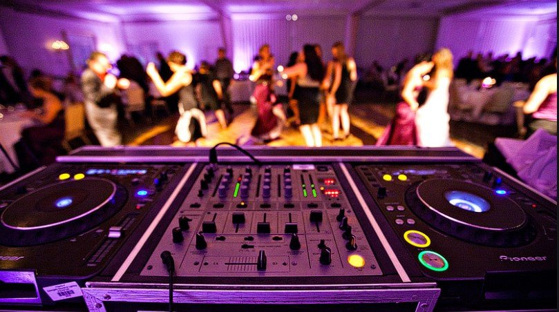 Close up picture of wedding DJ equipment with people dancing in the distance