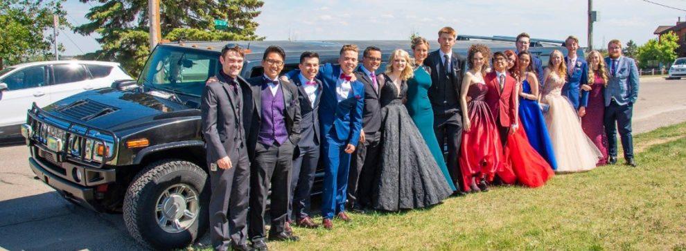 Group graduation photo with black Hummer Limo
