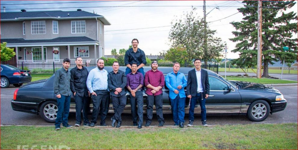 8 men standing in front and one on top of black Lincoln Stretch Limousine